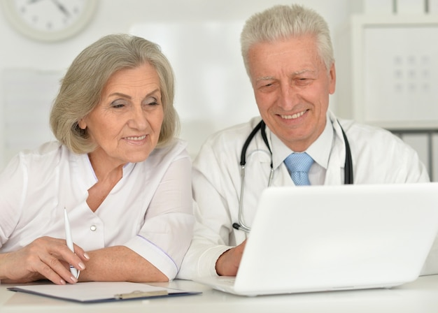 Mili starsi lekarze z laptopem w biurze