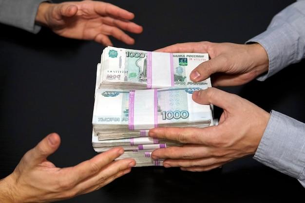 Milion rubli w męskich rękach. przekupstwo w rublach rosyjskich w ciemnym pokoju. pojęcie korupcji i przekupstwa. jeden człowiek daje pieniądze, inny je bierze. dobra oferta finansowa. sprzedaż gotówkowa