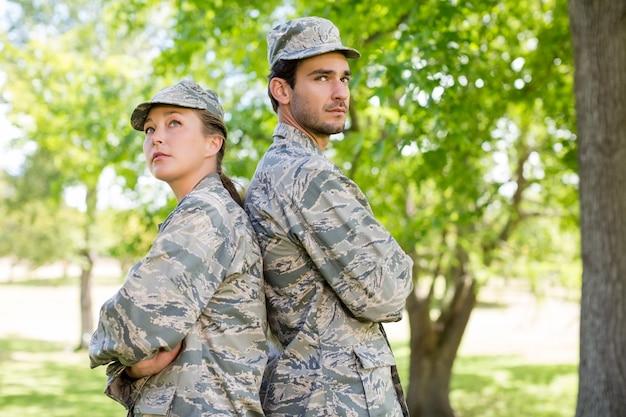 Militarna pary pozycja z rękami krzyżował w parku