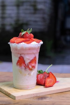 Milkshake z kawałkami truskawek, w plastikowym kubku, pyszny i świeży