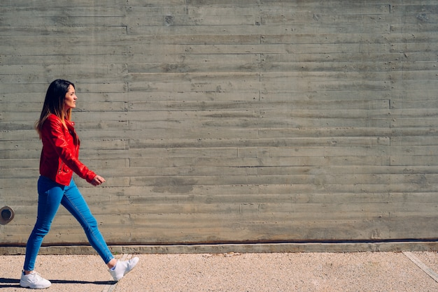 Millenial kobieta chodzi spokojnie w błękitnych i czerwonych cajgach obok cementowej ściany, szara tło kopii przestrzeń.