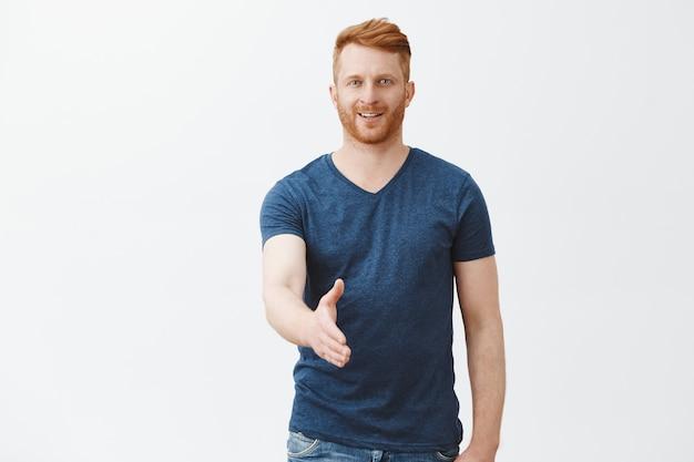 Miło cię poznać. uroczy i przyjazny przystojny rudy europejczyk z włosiem, wyciągający rękę w pozie uścisku dłoni