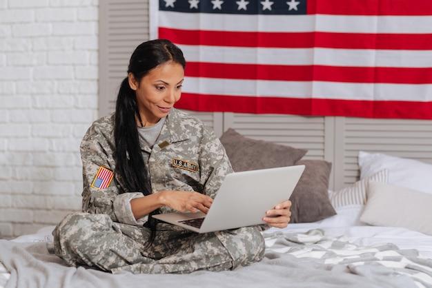 Miło cię widzieć. niesamowita, żywiołowa, emocjonalna dama prowadząca rozmowę wideo na komputerze, siedząc na łóżku i spędzając weekend w domu