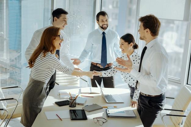 Miło cię widzieć. radośni młodzi koledzy, którzy wymieniają się uśmiechami, wręczają sobie uściski dłoni i witają się przed rozpoczęciem spotkania biznesowego