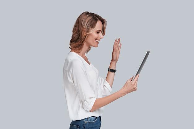 Miło cię widzieć! widok z boku pięknej młodej kobiety patrzącej na cyfrowy stół i machającej z uśmiechem na twarzy, stojąc na szarym tle