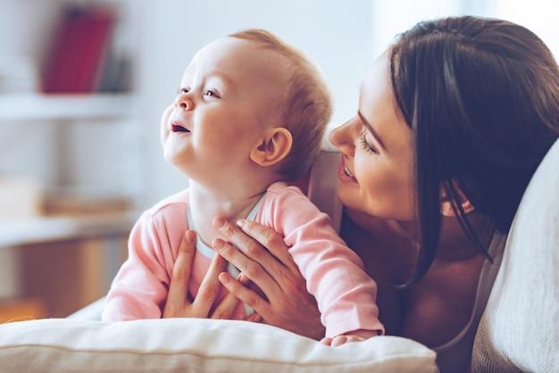Miło jest spędzać czas z mamą. wesoła młoda kobieta przytula swoją córeczkę i patrzy na nią z miłością, siedząc na kanapie w domu