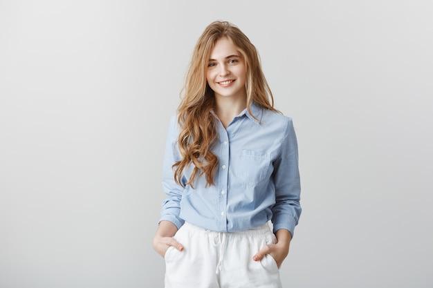 Miło mi poznać nowy zespół. portret sympatycznej, atrakcyjnej europejskiej kobiety o blond włosach w formalnej niebieskiej bluzce, trzymającej się za ręce w kieszeniach, słuchającej klienta podczas pracy w biurze