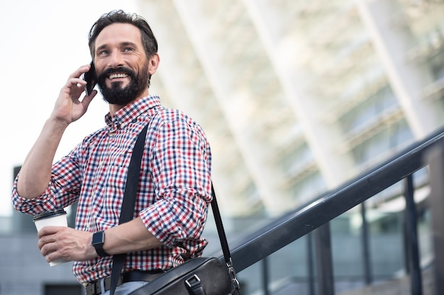 Miło z tobą rozmawiać. zadowolony przyjemny człowiek uśmiechnięty podczas rozmowy telefonicznej na zewnątrz