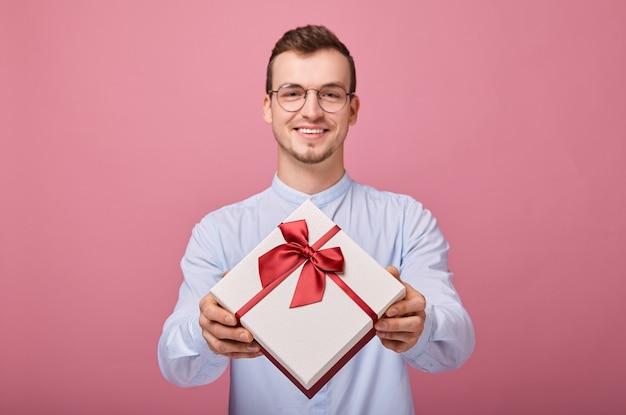 Miło zaskoczony mężczyzna w niebieskiej koszuli w okularach trzyma prezent w pudełku
