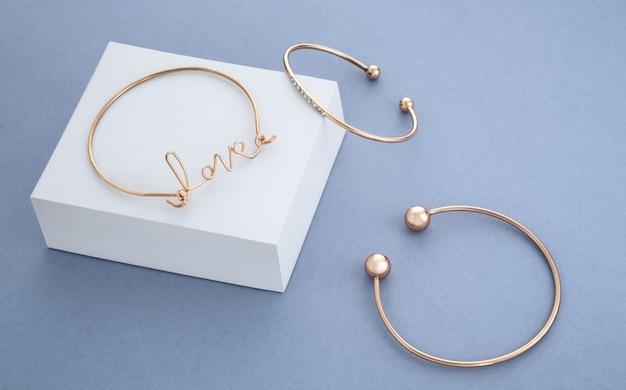 Miłość bransoletka w kształcie słowa na białym pudełku na niebieskim tle