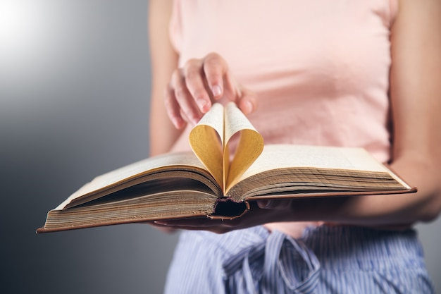 Miłość czytać książki koncepcja. kobieta trzymająca strony książki w sercu