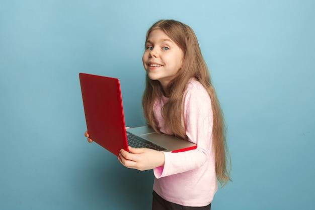 Miłość do komputera. teen dziewczyna z notatnikiem na niebieskim tle. wyraz twarzy i koncepcja emocji ludzi