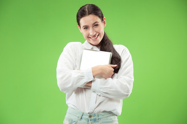 Miłość do koncepcji komputera. atrakcyjny portret kobiety do połowy długości z przodu, modna zielona ściana. młoda piękna emocjonalna kobieta. ludzkie emocje, wyraz twarzy