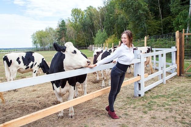Miłość do zwierząt. krowa i dziewczyna patrzą na siebie. strzał na zewnątrz