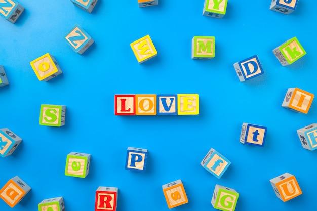 Miłość, drewniane kolorowe alfabet bloki na niebiesko, płasko, widok z góry