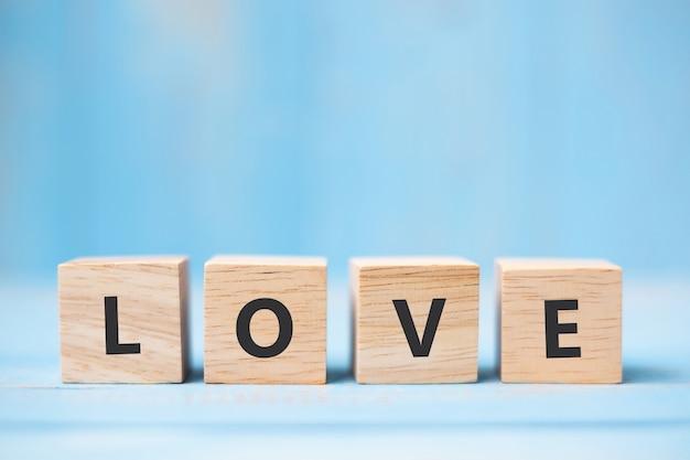 Miłość drewniani sześciany na błękita stołu tle
