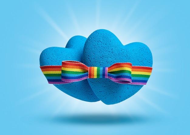 Miłość gejowska. dwa niebieskie serca są połączone tęczową kokardą lgbt. symbol taśmy dumy.