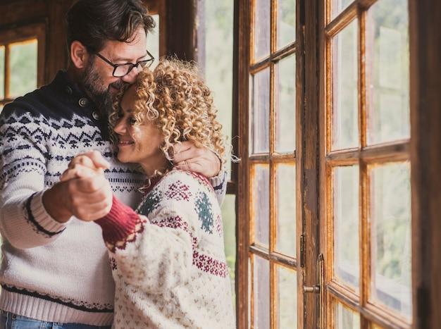 Miłość i beztroska para tańcząca w domu przy oknie