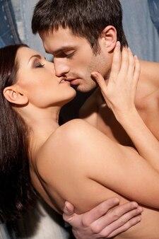 Miłość i pasja. piękna młoda para całuje bez koszuli, stojąc na tle dżinsów