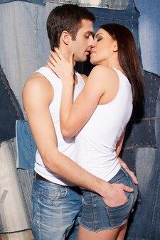 Miłość i pasja. piękna młoda para w podkoszulkach i dżinsach całuje stojąc na tle dżinsów