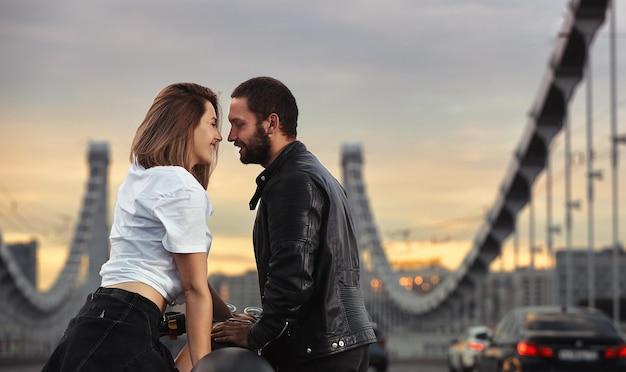 Miłość i romantyczna koncepcja. piękna para na motocyklu stoi naprzeciwko siebie na środku drogi na moście, na podwójnej bryle.
