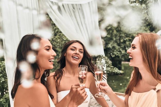 Miłość i szczęście! atrakcyjna młoda panna młoda wznosząca toast szampanem ze swoimi pięknymi druhnami, stojąca razem na zewnątrz