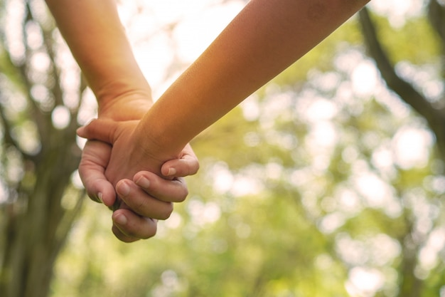 Miłość i szczęśliwa para, z bliska trzymając rękę razem jako chodzenie w parku z zachodem słońca