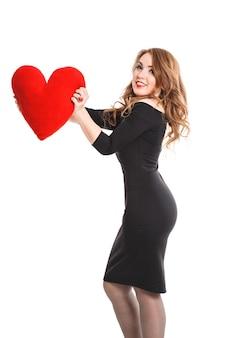 Miłość i walentynki. sexy blond kobieta z czerwonymi ustami i sercem w czarnej sukience uśmiechnięty ładny i urocza, na białym tle na biały, pozuje do aparatu, makijaż moda luksusowy. walentynki.