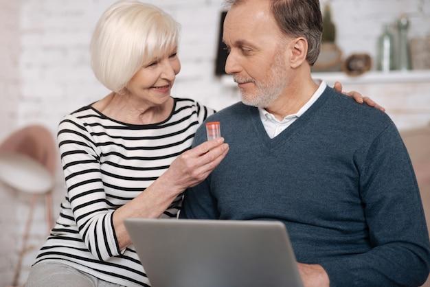 Miłość i wsparcie. miła piękna starsza pani dająca lekarstwo ukochanemu mężowi za pomocą laptopa siedząc na łóżku.