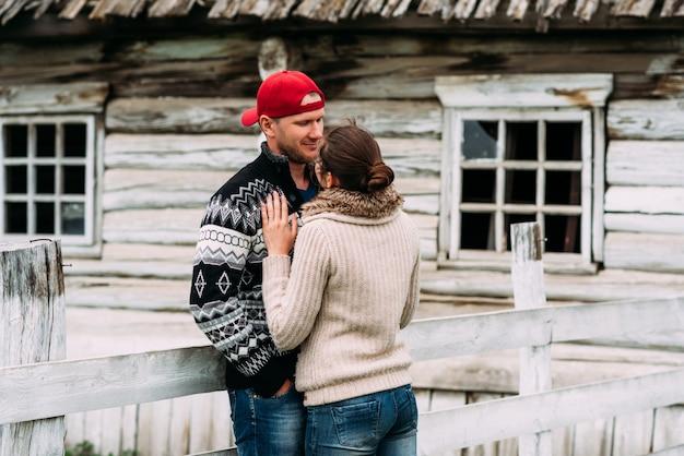 Miłość i związek między kobietą a mężczyzną. pojęcie młodej rodziny. para zakochanych przytula. mężczyzna całuje swoją kobietę. szczęśliwa para na zewnątrz. młoda para we wsi