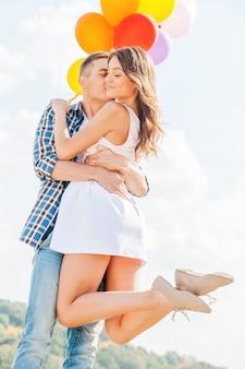 Miłość jest w powietrzu. mężczyzna trzymający piękną młodą kobietę i balony podczas jej całowania