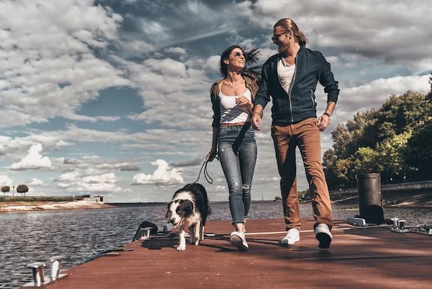 Miłość jest w powietrzu. pełna długość pięknej młodej pary patrzącej na siebie i uśmiechającej się podczas spaceru z psem brzegiem rzeki