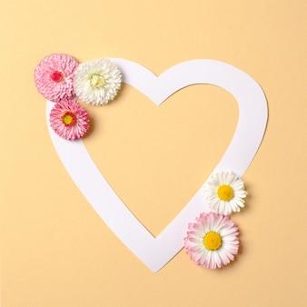 Miłość koncepcja natury. kwiaty stokrotki i biała kartka papieru w kształcie serca na pastelowym żółtym tle.
