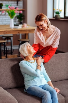 Miłość między matką a córką. szczęśliwy, urzekający stylowy dorosły dama czule palming dłoń matki i trzymający głowę, gdy rozmawiają w salonie.