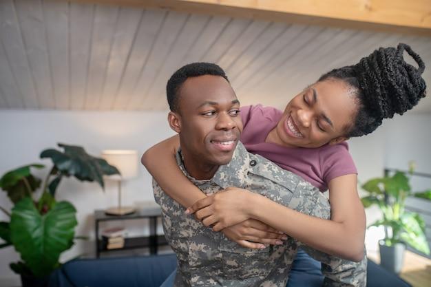 Miłość. młody, ciemnoskóry, silny wojskowy i piękna żona w wesołym nastroju, patrzący na siebie z miłością w domu