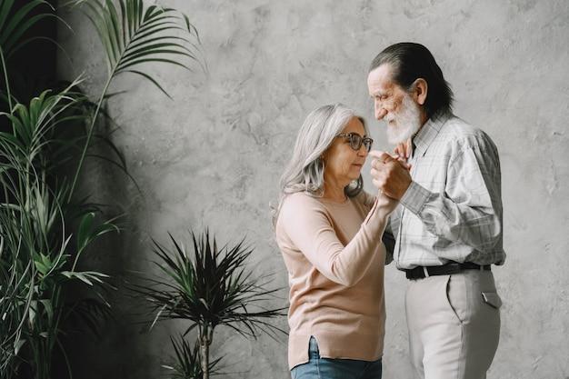 Miłość nigdy się nie starzeje. radosny aktywny stary emerytowany romantyczna para taniec w salonie.