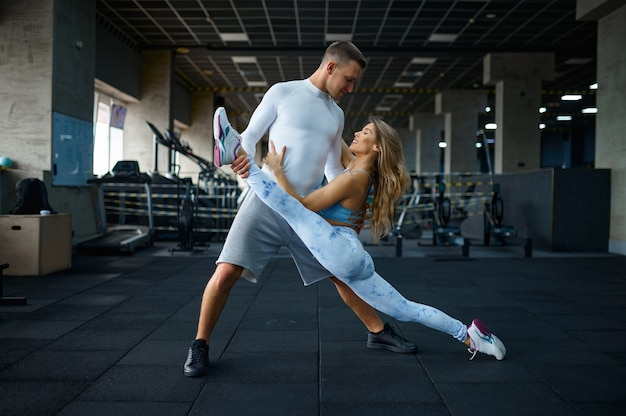 Miłość para robi ćwiczenia rozciągające w siłowni