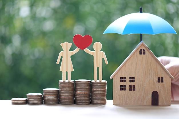 Miłość para trzymająca kształt serca stojący na stosie monet pieniędzy z modelowym domem pod parasolem na naturalnym zielonym tle