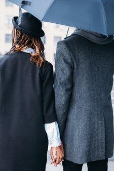 Miłość para w deszczowy dzień widok z tyłu. styl mody. nierozpoznawalni stylowi ludzie w szaro-czarnych suknach, kapryśna pogoda, silny związek