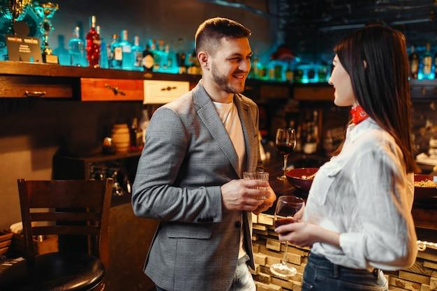 Miłość para z napojami alkoholowymi rozmawiająca przy barze, romantyczny wieczór mężczyzny i kobiety.