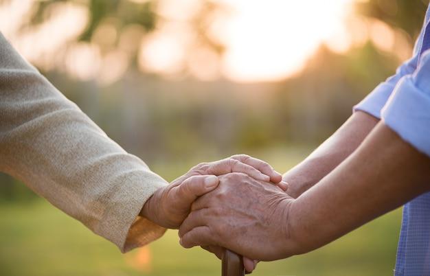 Miłość przyjaźń i walentynki koncepcja szczęśliwa para starszych trzymająca się za rękę
