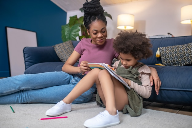 Miłość, troska. uśmiechnięta młoda afroamerykańska kobieta mama ogląda malowanie małej dziewczynki, skupiając się na siedzeniu razem na podłodze w domu