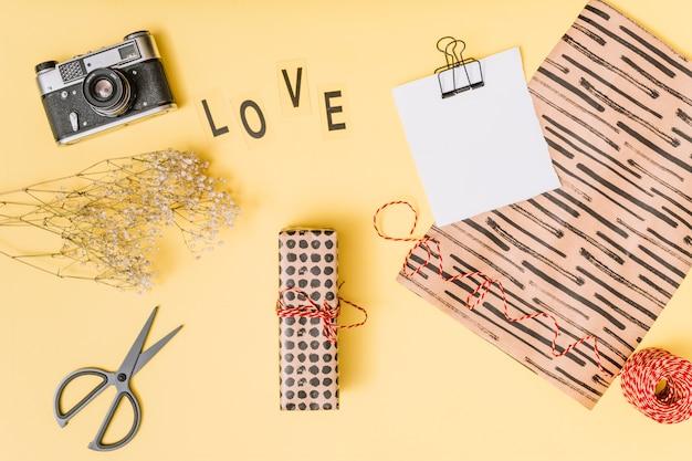 Miłość tytuł w pobliżu nożyczek, aparatu, pudełko, rośliny i papier