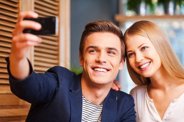 Miłość w centrum uwagi. piękna młoda kochająca para łącząca się ze sobą w kawiarni, podczas gdy mężczyzna robi selfie za pomocą smartfona