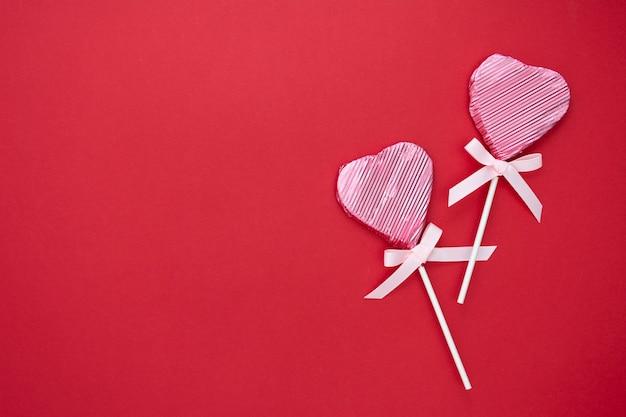 Miłość, walentynki makiety, płaskie leżał, różowy lizak w kształcie serca na białym tle na czerwonym tle, miejsce.