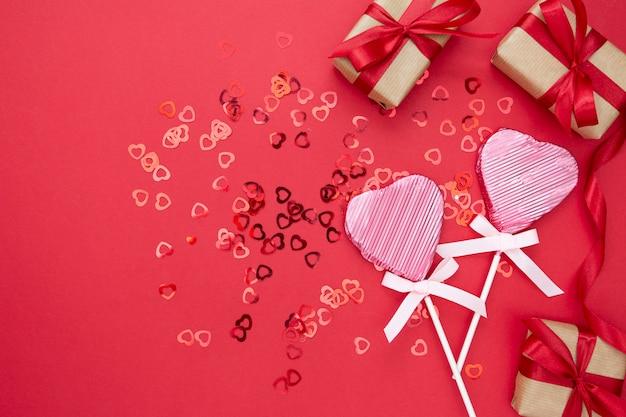 Miłość, walentynki makiety, z lollipop w kształcie serca, pudełko i brokat na białym tle na czerwonym tle, miejsce.