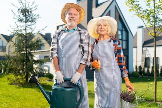 Miłość. wesoła emeryci, sympatyczna para uśmiechnięta spędzająca dzień w ogrodzie