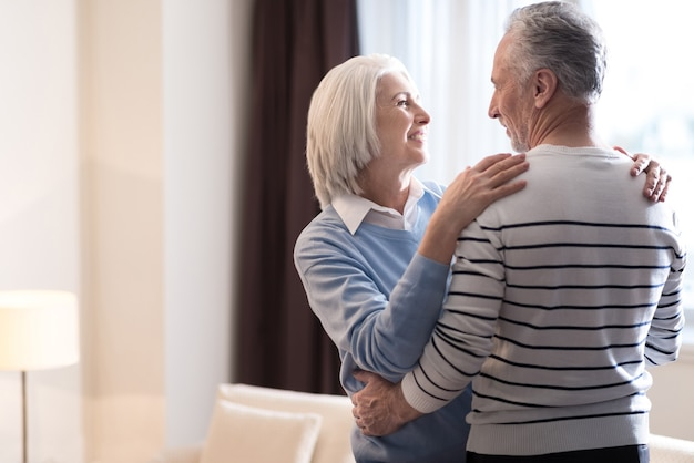 Miłość. wesoła, uśmiechnięta para w wieku tańczy w domu, patrząc na siebie i przytulanie