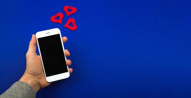 Miłość wiadomość na wakacjach, karta walentynki, makieta z mężczyzną trzymającego smartfon z powiadomieniem w formie serc. zdjęcie wysokiej jakości