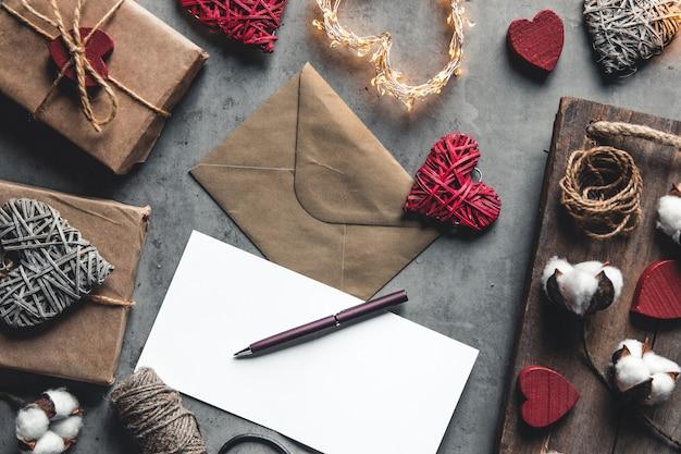 Miłość wiadomość walentynki. przygotowanie, pakowanie prezentów, bawełniane kwiaty i pocztówka